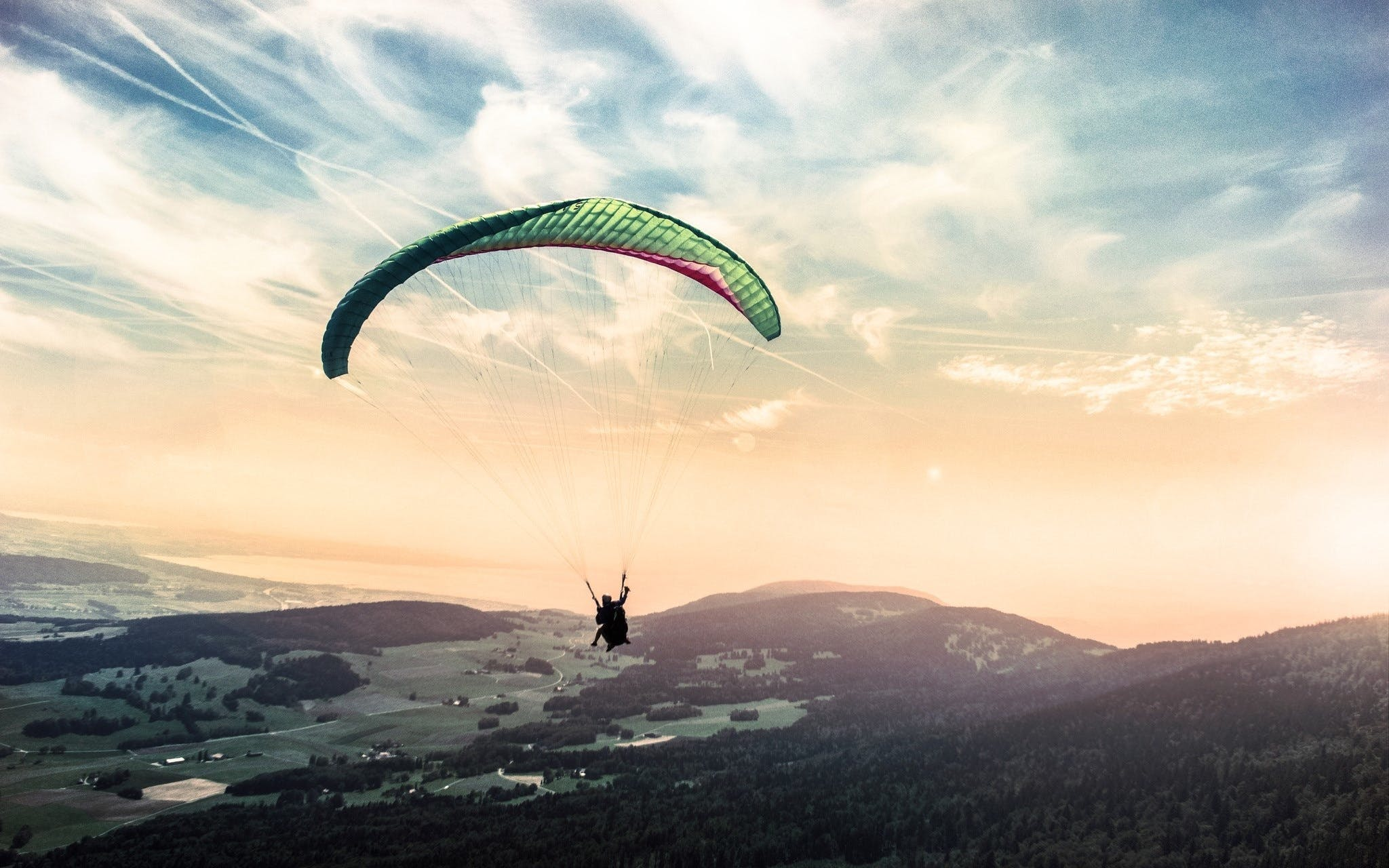 Person Riding Paragliding Under Blue and White Cloudy Sky