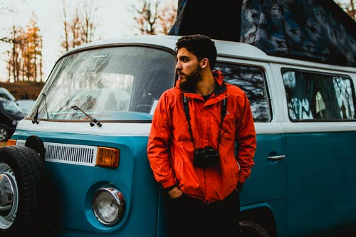Man in Orange Jacket Standing Beside A Volkswagen Van