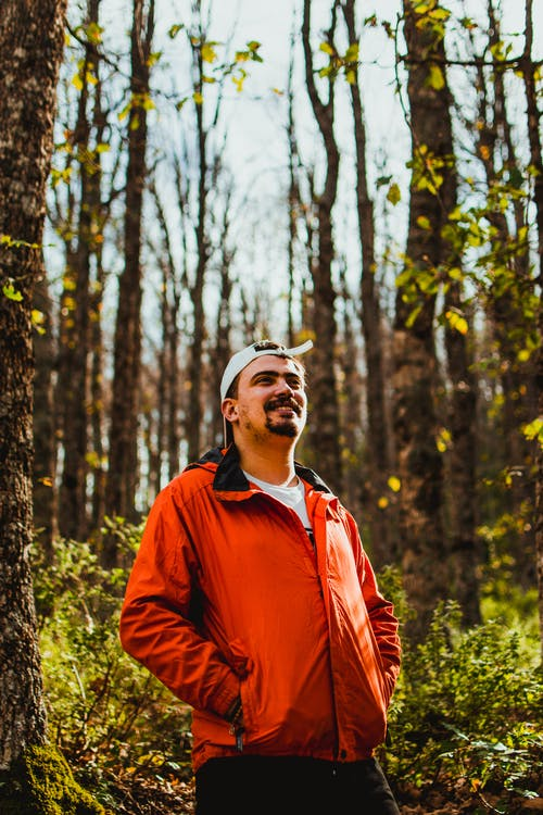 Man in Red Jacket Standing Near Trees