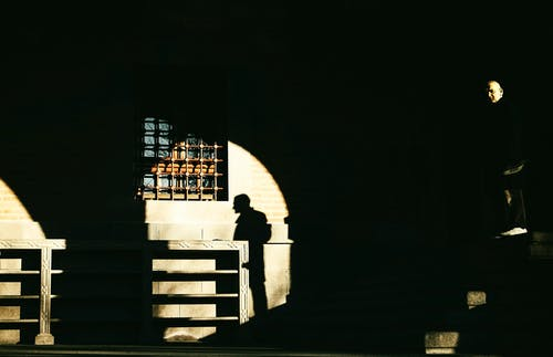 Silhouette of Person Standing on Balcony during Night Time