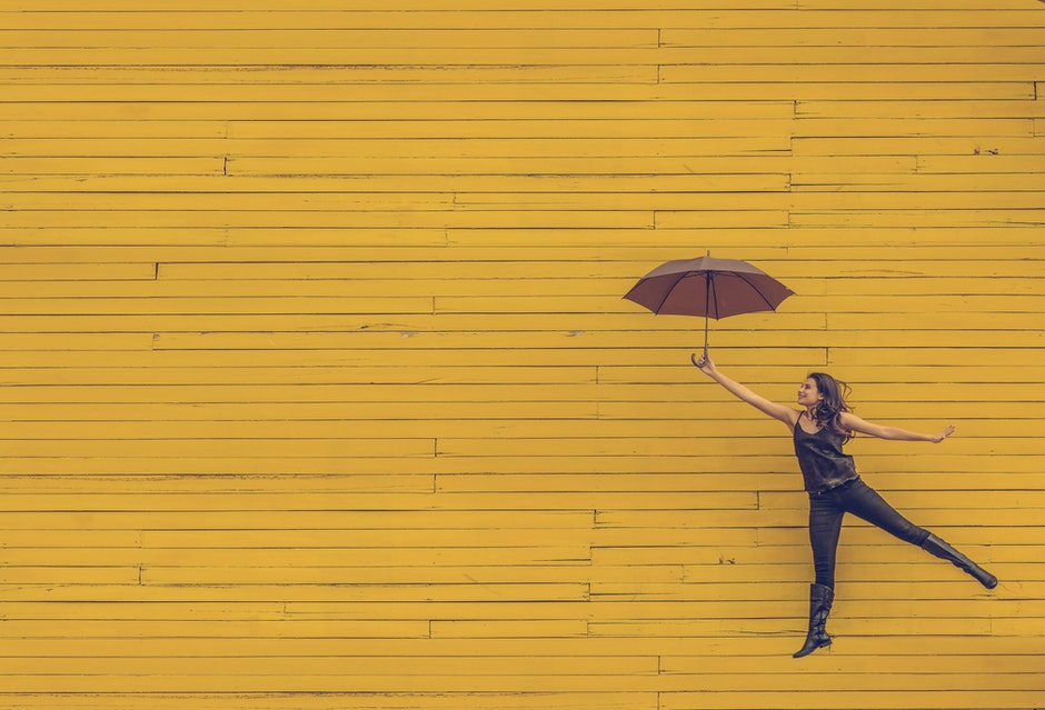 Woman in Black Tank Top Holding an Umbrella in Front of Yellow Concrete Wall