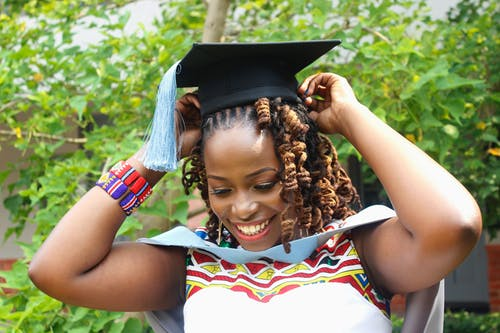 Photo of Woman Smiling While Wearing Square Academic Cap