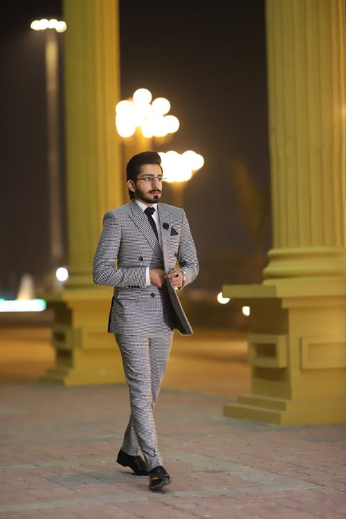 Photo Of Man Walking In Grey Suit