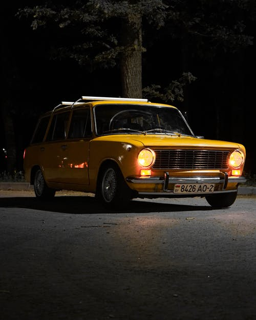 Yellow Vintage Car Parked on Road during Night Time