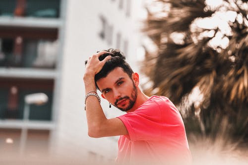 Shallow Focus Photo of Man in Pink Shirt While Holding His Hair