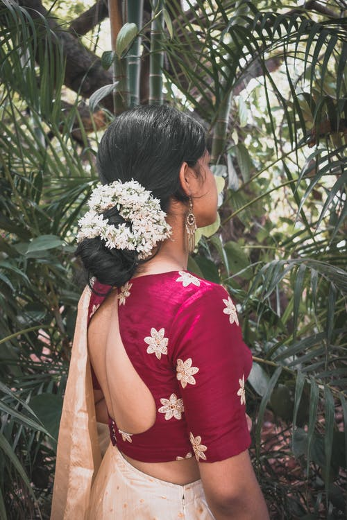 Woman in Red and White Floral Top Standing Near Green Plants