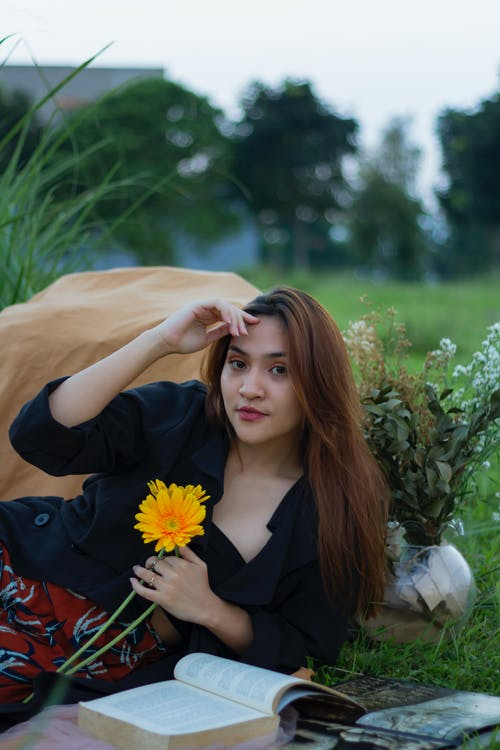 Photo Of Woman Holding Yellow Flower