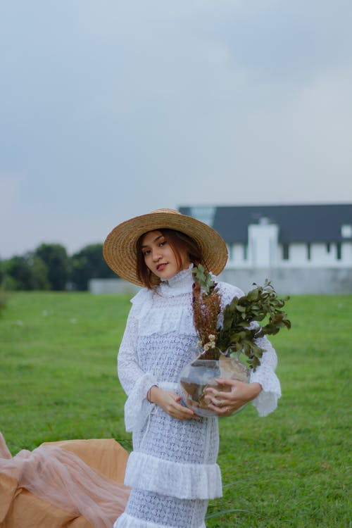 Photo Of Woman Carrying Vase