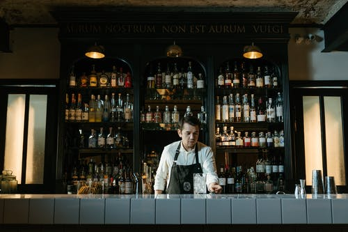 Man in White Dress Shirt Standing in Front of Counter
