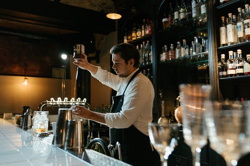 Man in White Long Sleeve Shirt Pouring Wine on Clear Wine Glass