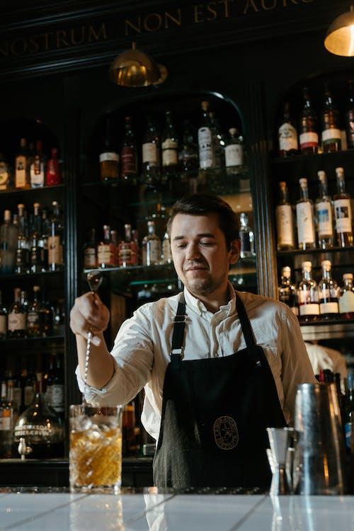 Man in White Long Sleeve Shirt Holding Glass Bottle
