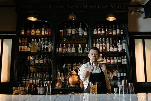 Man in White Dress Shirt Sitting on Chair in Front of Bar Counter
