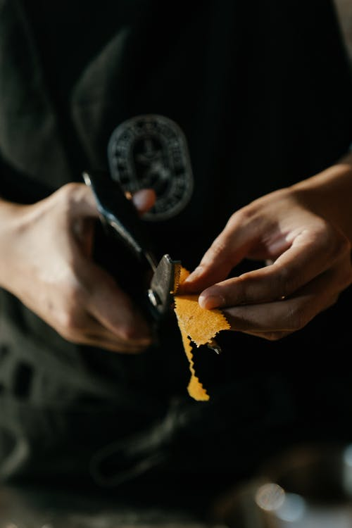 Person Holding Yellow and Black Textile