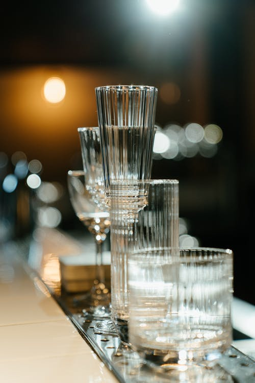 Clear Wine Glasses on Brown Wooden Table