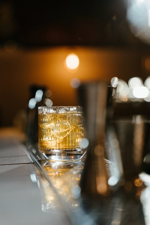 Clear Drinking Glass With Brown Liquid on Table