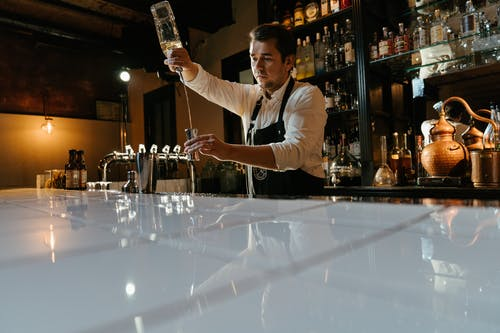 Man in White Long Sleeve Shirt Holding Bottle Pouring Water on Clear Drinking Glass