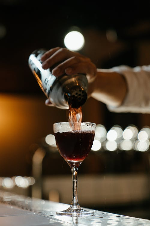 Person Pouring Red Wine on Clear Drinking Glass