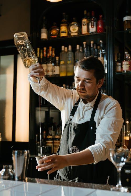 Man in White Dress Shirt Holding Clear Glass Bottle