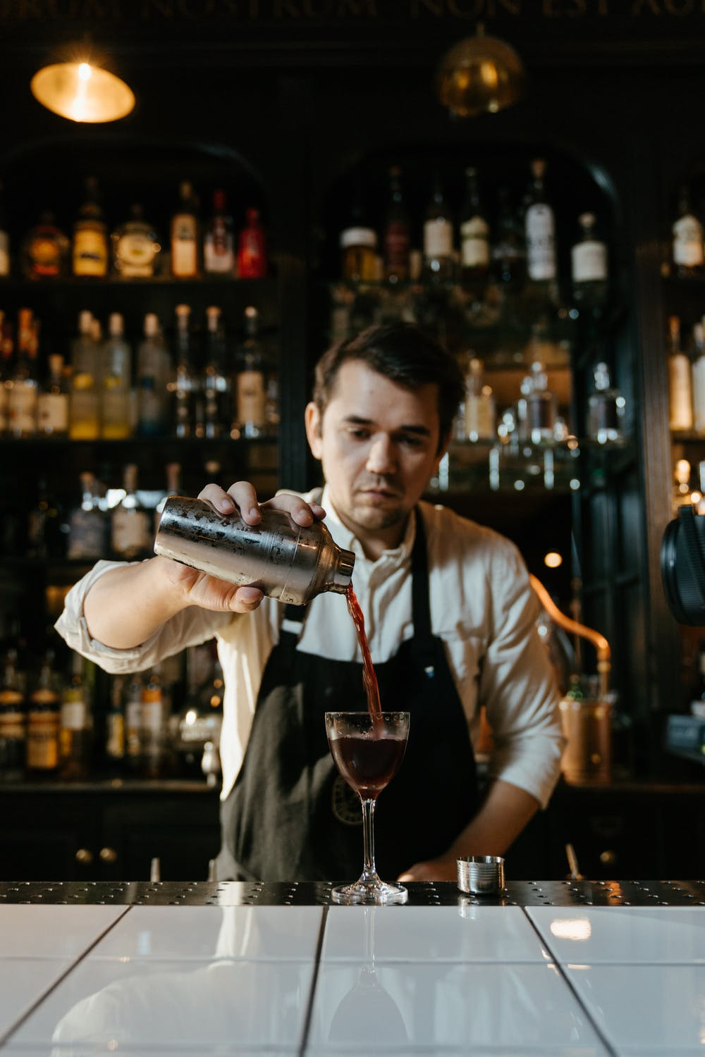 A bartender holding the bottle and drinking glass.   Photo: Pexels