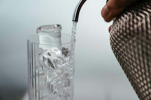 Person Holding Clear Drinking Glass