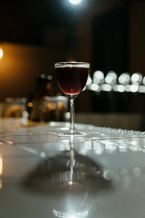 Clear Wine Glass With Red Wine on Table