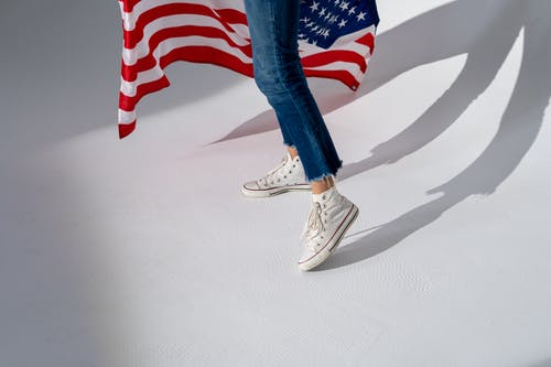 Person in Blue Denim Jeans and White Sneakers Standing Beside Us Flag
