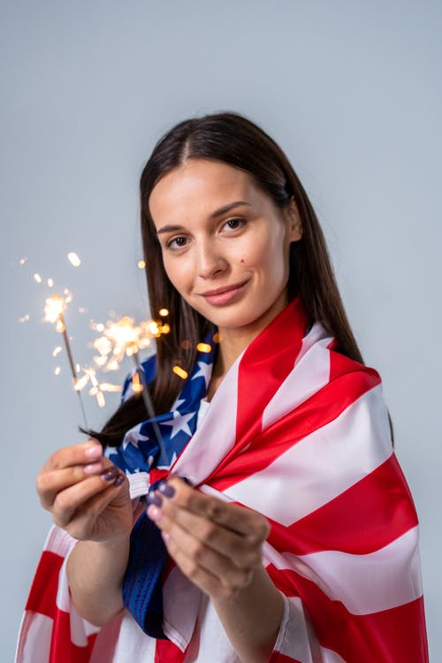 Woman With an American Flag Holding Sparklers