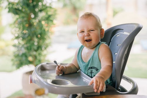 Photo Of Baby Sitting On High Chair