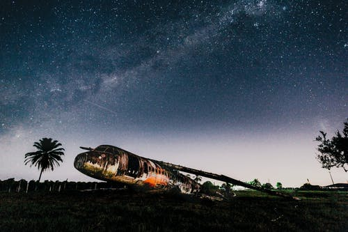 Crashed airplane on land under bright sky in evening