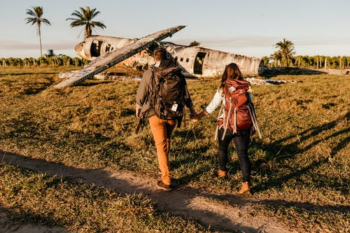 Unrecognizable tourists walking on land near crashed airplane