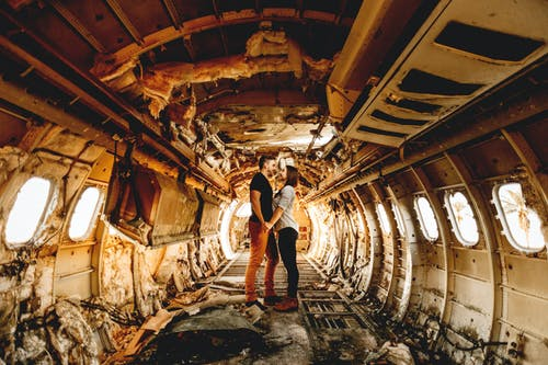 Side view of anonymous content couple of travelers holding hands in abandoned aircraft after accident while looking at each other