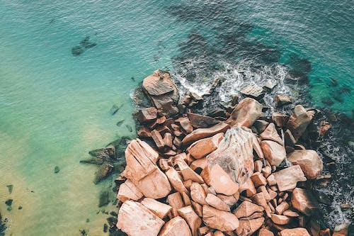 Rough rocks in waving ocean water in daylight