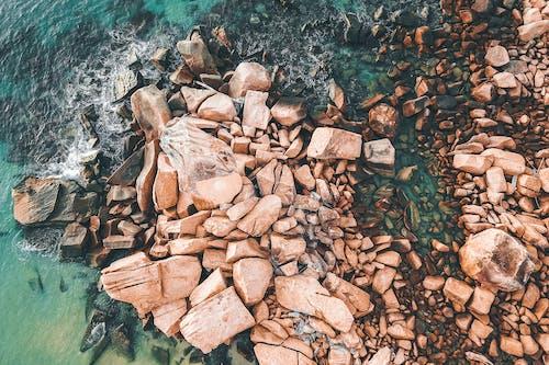 Sea waves splashing on stony boulders