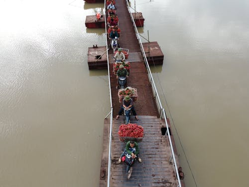 From above of people transporting food in baskets on motorbikes riding on float bridge above rippled river