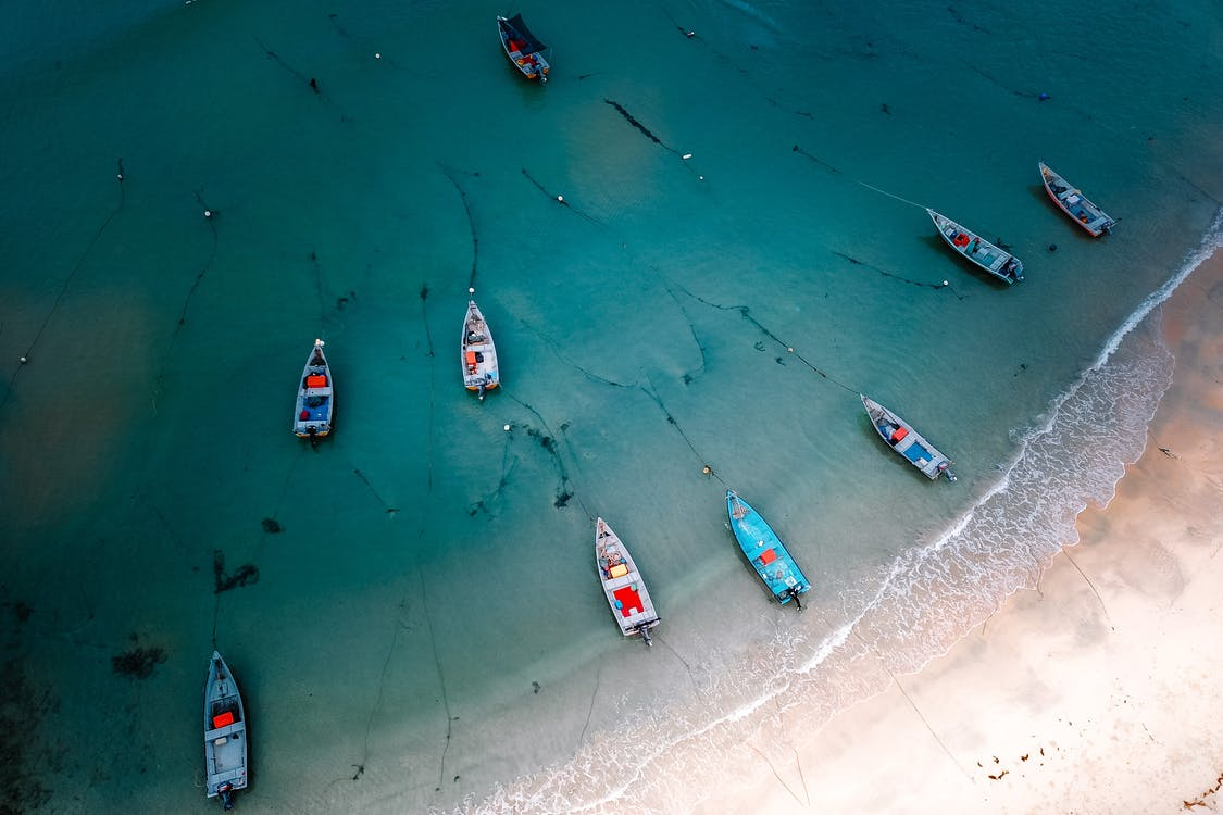 Boats floating near sandy sea coast