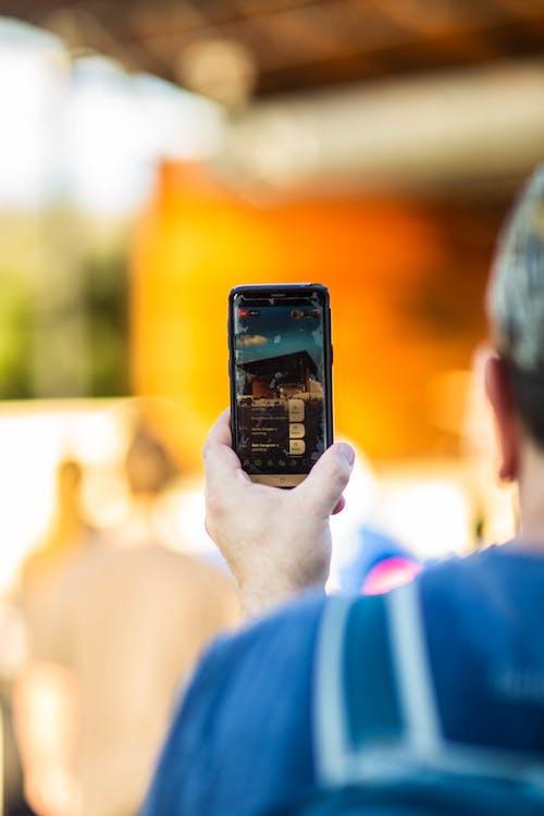 Crop man taking photo on smartphone