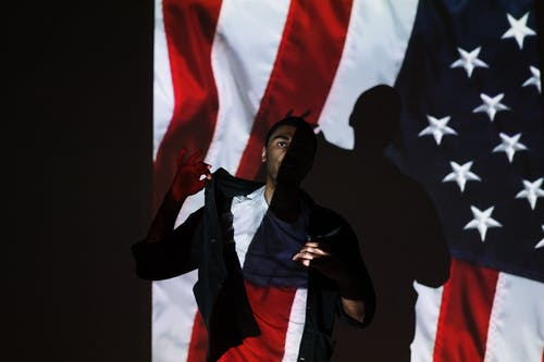 Man Standing in Front of a Projection of the American Flag