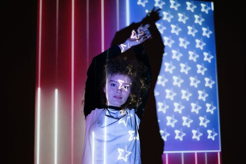 Woman Standing in Front of a Projection of the American Flag