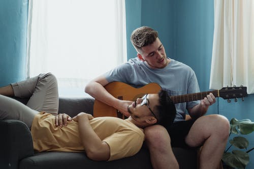 Man Playing Guitar While Another Man Rests His Head on His Leg