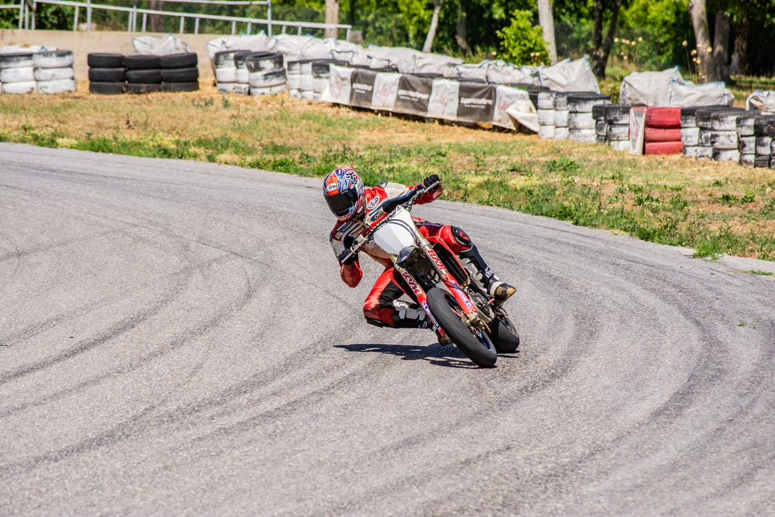 Man in Red and Black Motorcycle Suit Riding on Red Sports Bike