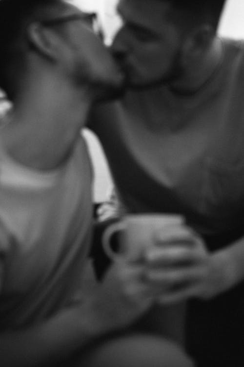 Burry Grayscale Photo of Two Men Kissing