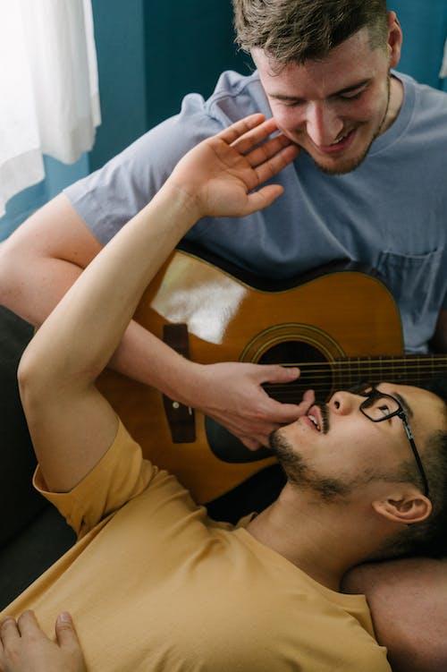 Безкоштовне стокове фото на тему «азіатський чоловік, акустична гітара, білошкірий, близькість»