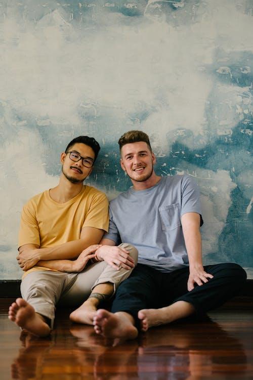 Two happy Men Sitting on the Floor