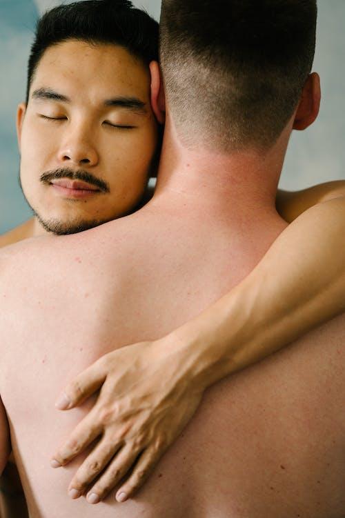 Two Topless Men Hugging