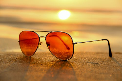 94dc4e52094 Red Lens Sunglasses on Sand Near Sea at Sunset Selective Focus Photography