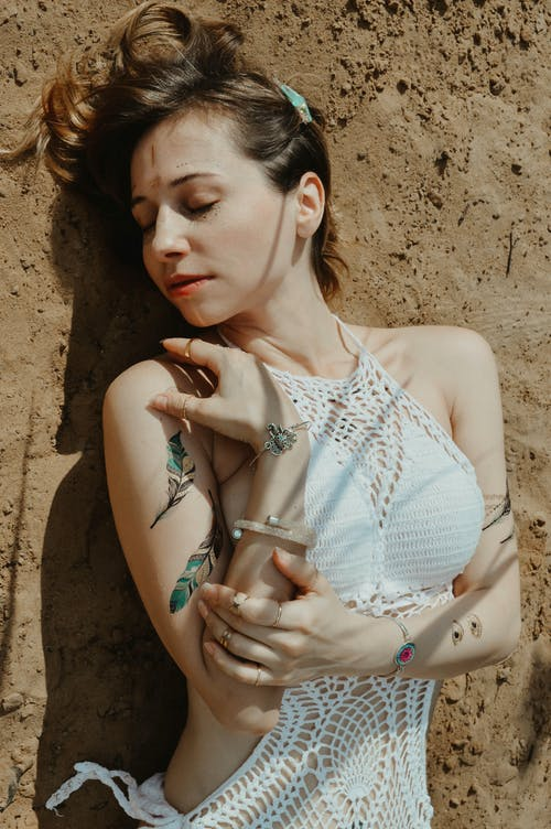 Charming woman lying on sand shore in sunlight