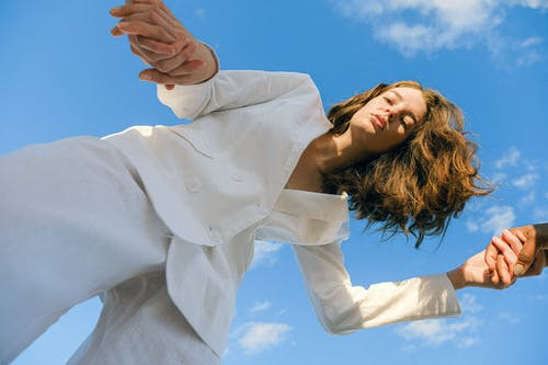 Woman in White Long Sleeve Shirt Covering Her Face With Her Hair