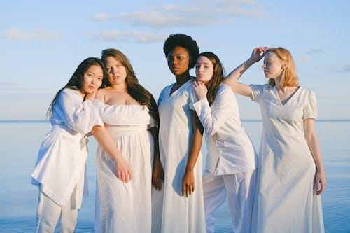 3 Women in White Dresses Posing for Photo