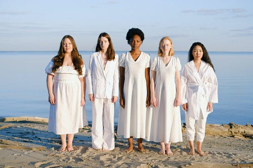 Group of Women in White Dresses Standing on Gray Sand