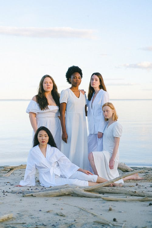 4 Women in White Robe Standing on Beach